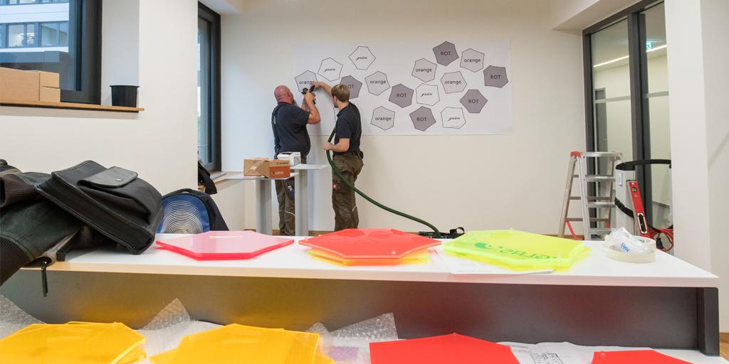 Zwei Monteure montieren mehrteiliges Wandobjekt - Projekt tesa SE