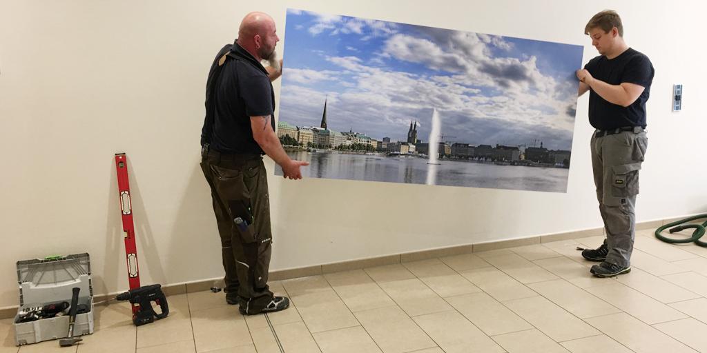 Zwei Monteure hängen einen Fotodruck an die Wand
