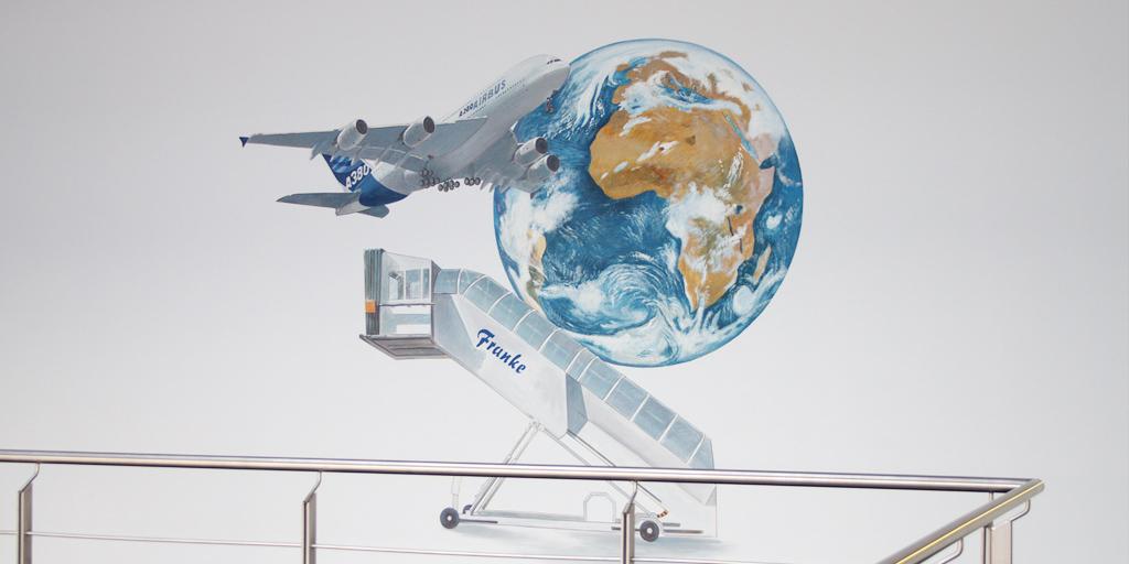 Wandmalerei von Uwe Fehrmann mit Flugzeug und Weltkugel